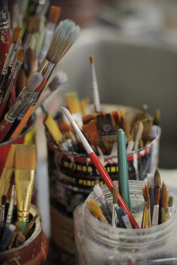 Dirty paintbrushes in a jar