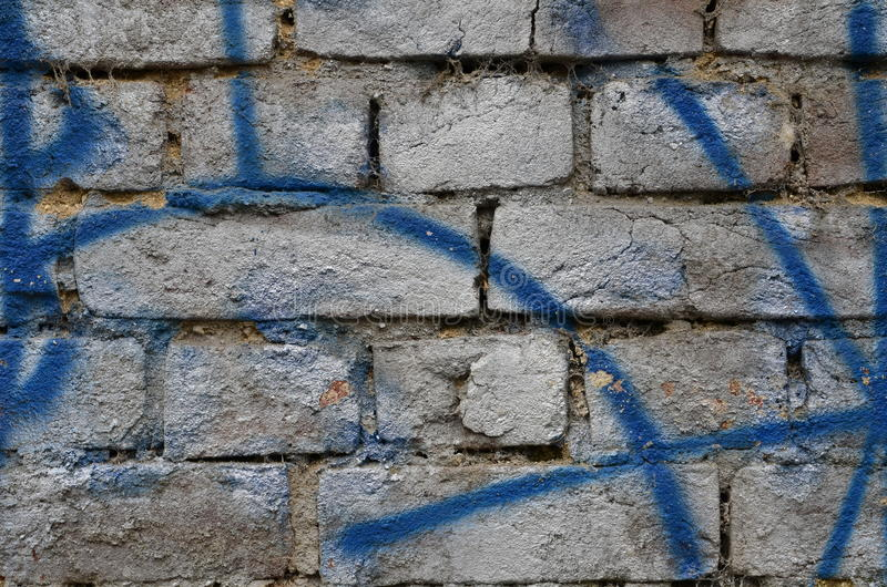 Dirty painted brick wall. Old brick wall airbrushed with silver and blue paint royalty free stock photography