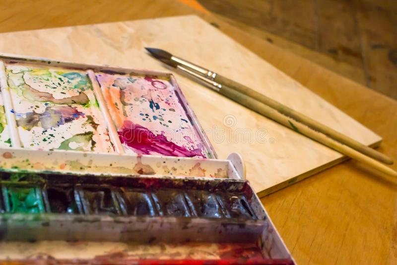 Dirty pallet and watercolor set with two wooden brushes on the table and a mug of water. Dirty pallet and watercolor set with two thin wooden brushes on the stock images