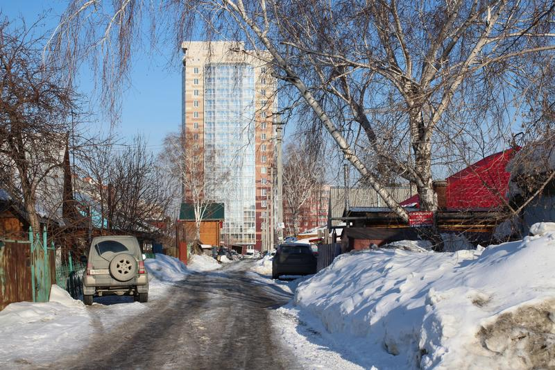 Dirty passage near private houses in the spring in Novosibirsk Parkhomenko street with parked cars leads to the city high-rise stock photos