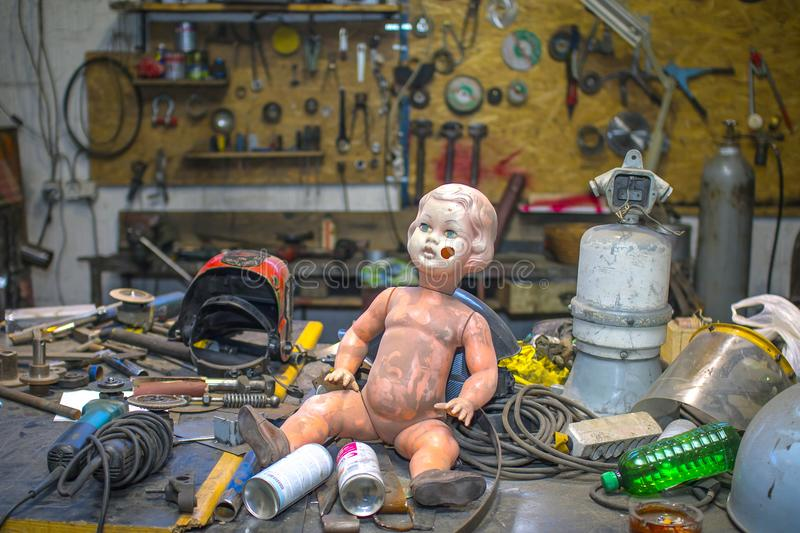 Dirty plastic baby doll posing inside of a metal shop royalty free stock images
