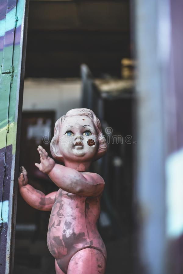 Dirty plastic naked baby doll standing by the door at the metal shop looking eerie and hunted weaving royalty free stock photos