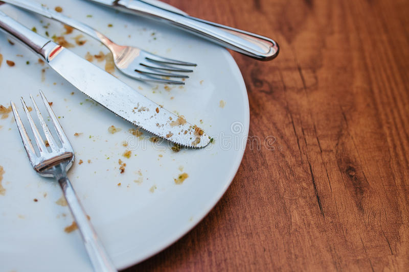 Dirty plate. Empty plate after eating place on wooden table in coffee shop. royalty free stock photos