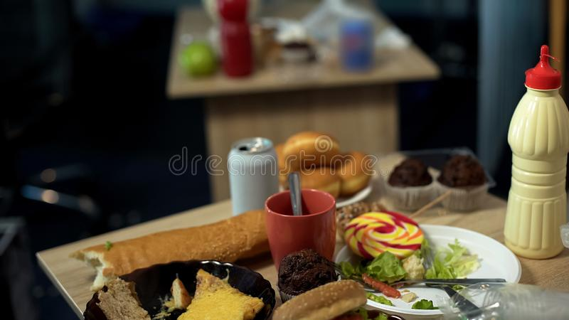 Dirty plates full of greasy junk food leftovers standing on messy table disorder. Stock photo stock photos