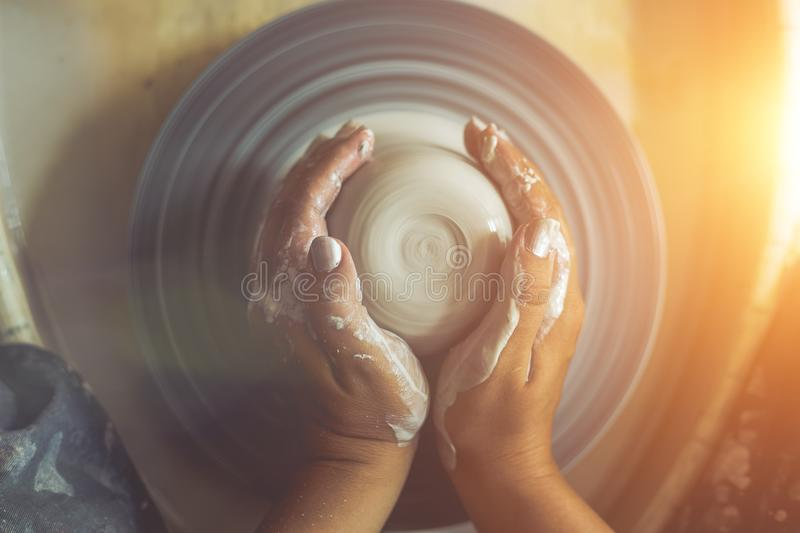 Dirty potter hands works with clay on pottery wheel, top view. In sunlight, toned royalty free stock photography