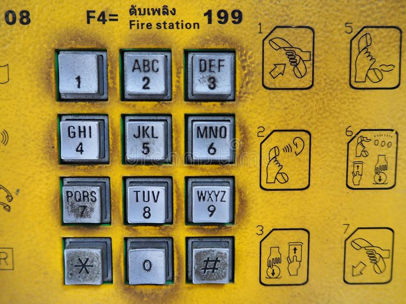 Dirty public telephone silver keypad with yellow background sign instruction royalty free stock photo