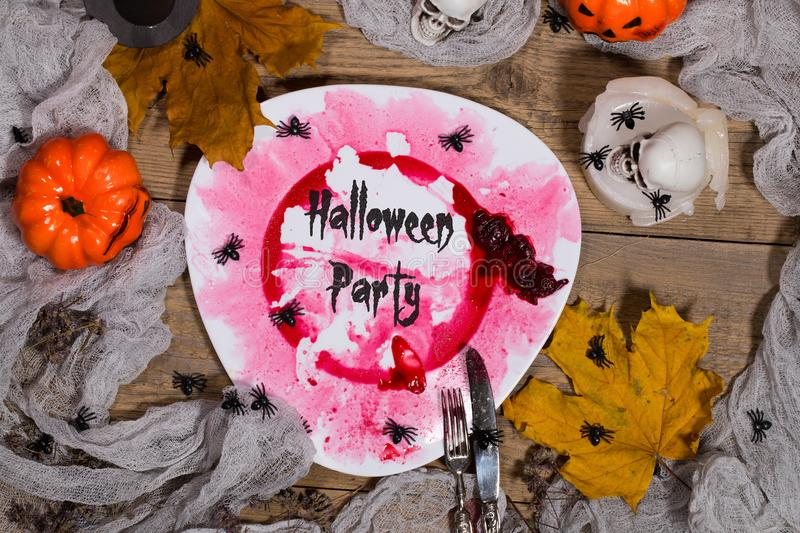 Halloween Party. Dirty red plate with silver cutlery on Halloween table. , plate stock photos