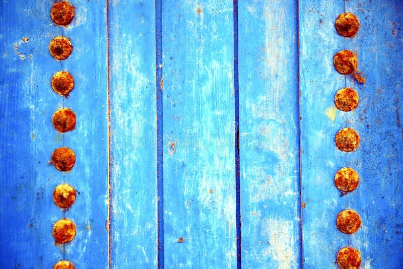 Dirty rev av målarfärg i den blåa wood dörren och rostigt arkivbilder