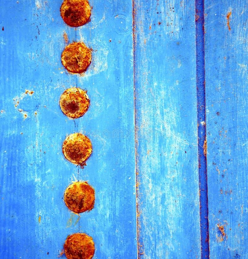 Dirty rev av målarfärg i den blåa wood dörren, och rostigt spika arkivfoto