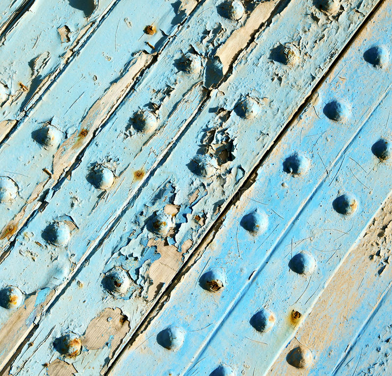 Dirty rev av målarfärg i den blåa wood dörren, och rostigt spika arkivbild