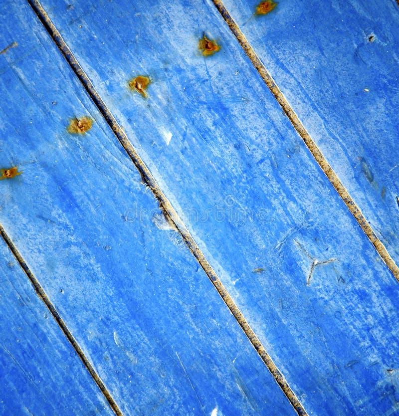 Dirty rev av målarfärg i den blåa wood dörren, och rostigt spika fotografering för bildbyråer