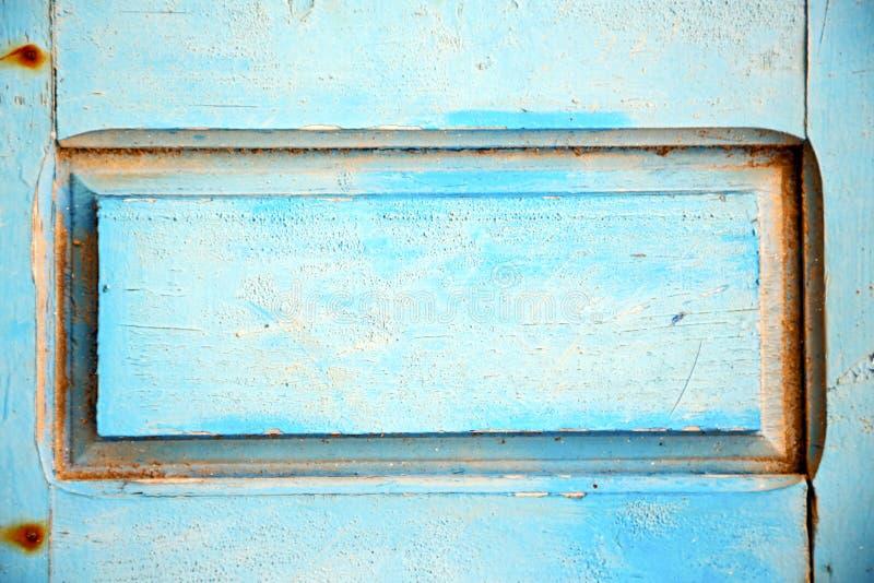 Dirty rev av målarfärg i den wood dörren, och rostigt spika arkivbilder