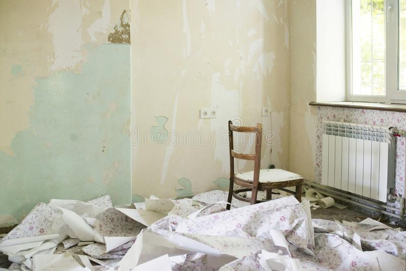 Dirty room with torn wallpaper on the floor royalty free stock photography