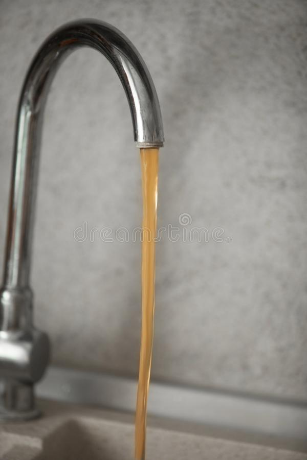 Dirty, rusty water flows from the tap stock photography