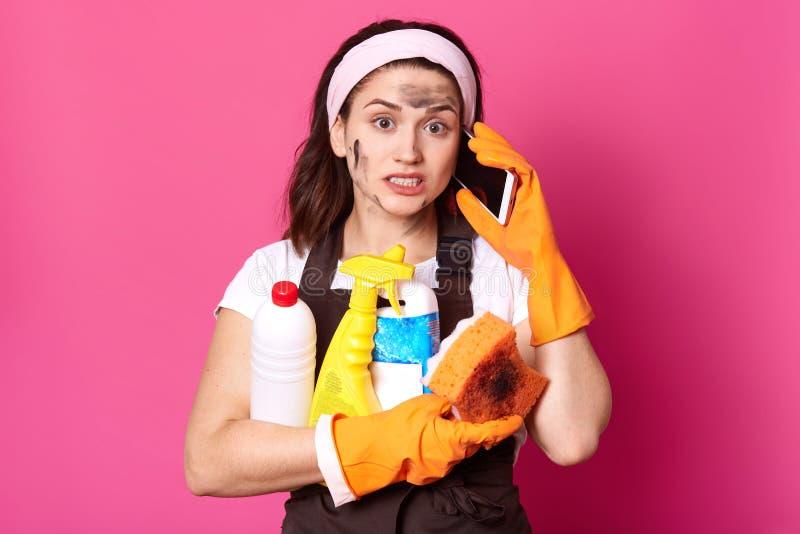 Dirty rymmer den utmattade hemmafrun massor av rengörande flytande i händer och att tala över telefonen som uppmärksamt lyssnar t arkivbilder