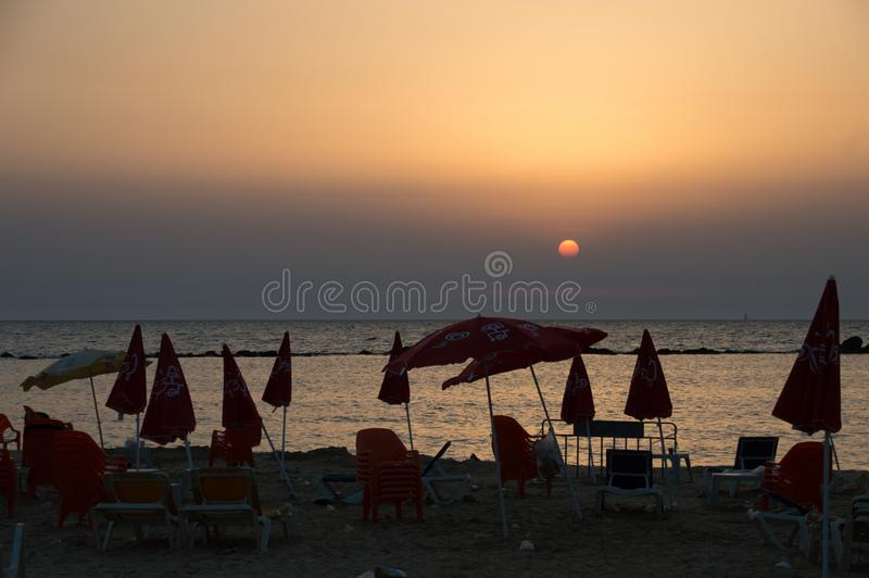 Dirty sandy beach, filled with plastic trash red parasols and chairs in summer sunset stock photography