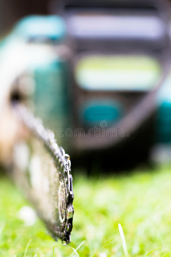 Dirty in sawdust chain saw on grass in garden close up royalty free stock photography