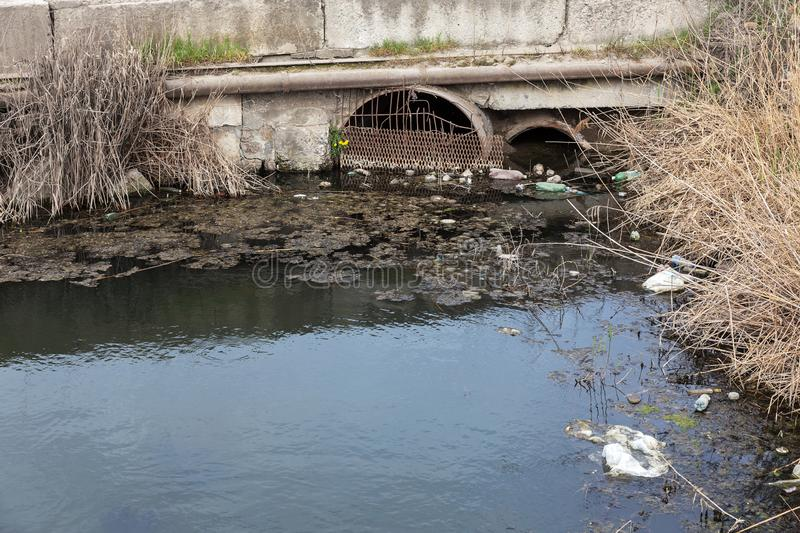 Dirty sewage and household rubbish in small river, irrigation channel causes rapid growth of algae. Water pollution. Ecological pr. Oblem. Problem of plastic royalty free stock photos
