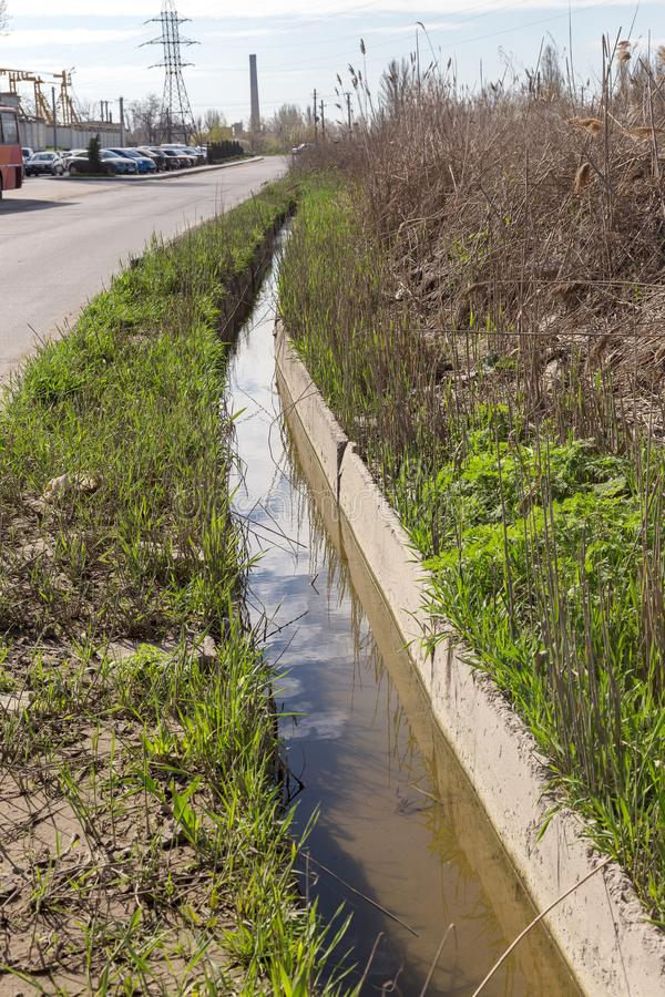 Dirty sewage and household rubbish in small river, irrigation channel causes rapid growth of algae. Water pollution. Ecological pr. Oblem. Problem of plastic royalty free stock images