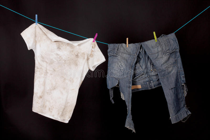 Dirty shirt and trousers. Hanging to dry on a black background stock photo