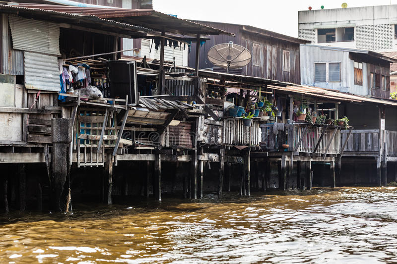 Dirty slum. Wooden slums on stilts on the riverside of Chao Praya River in Bangkok, Thailand stock photos