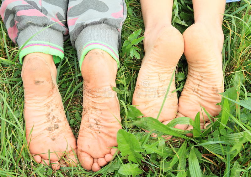 Dirty soles of bare feet. Four dirty soles of bare feet of two little girls
