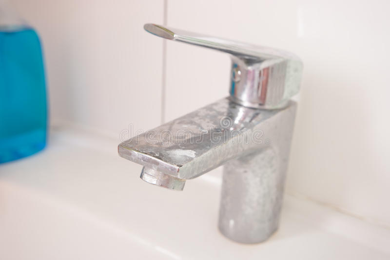 Dirty steel faucet in the bathroom. royalty free stock images