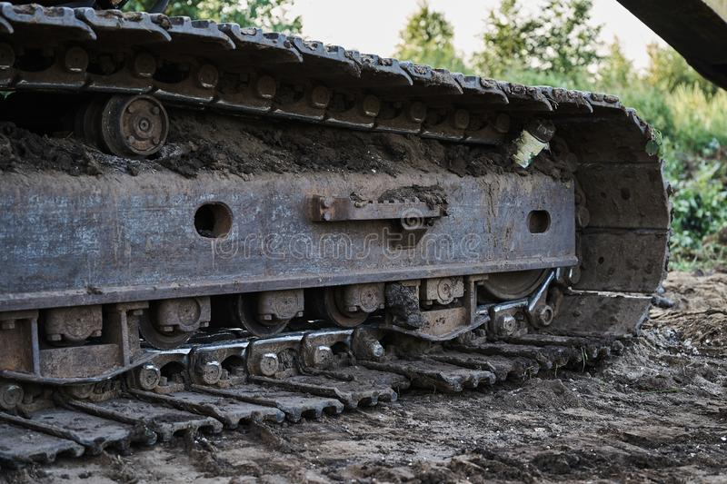 Dirty tracks of old excavator close up stock photography