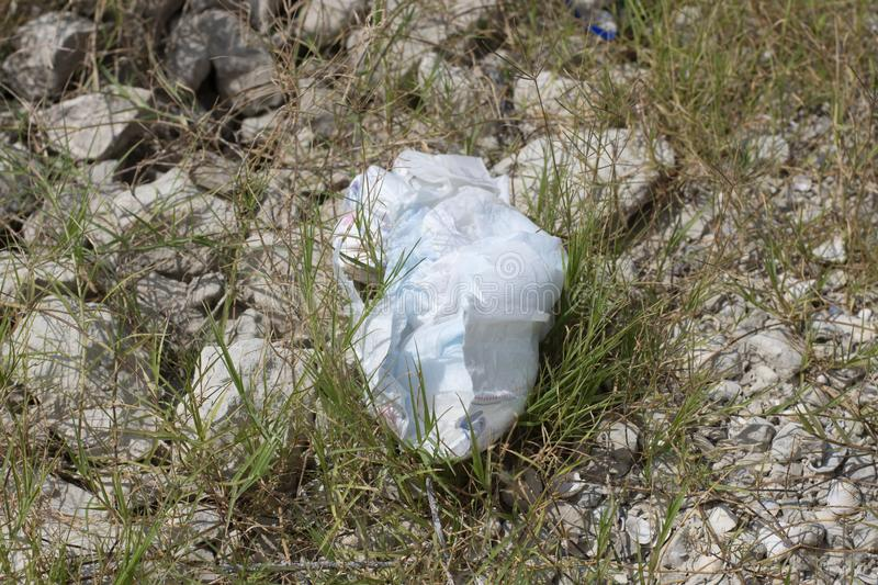 Dirty diaper littering lake shore royalty free stock photography