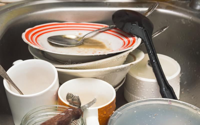 Unwashed kitchen utensils and dishes in the sink royalty free stock photo