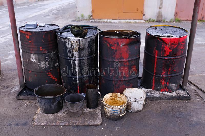Dirty used colorful oil drums are modified to look like garbage cans in the engine room. Used engine oil in large barrels, buckets. Or containers. Environmental royalty free stock image