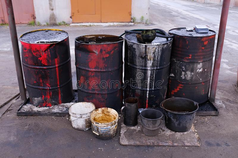 Dirty used colorful oil drums are modified to look like garbage cans in the engine room. Used engine oil in large barrels, buckets. Or containers. Environmental royalty free stock images