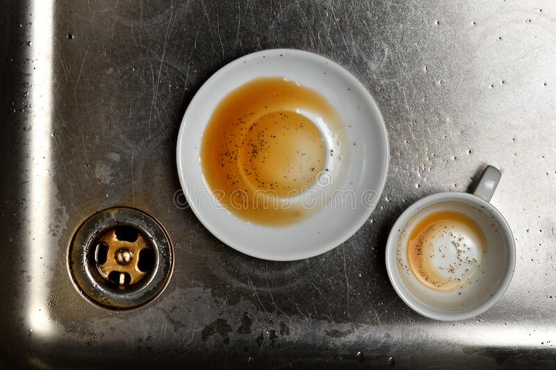 Dirty used white porcelain cup and saucer in a stainless steel kitchen sink. Spout, wash basin and coffee remains. Dishwasher in restaurant stock image