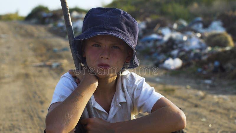 Dirty vänd mot pojke som huka sig ned på nedgrävning av sopor arkivfoton
