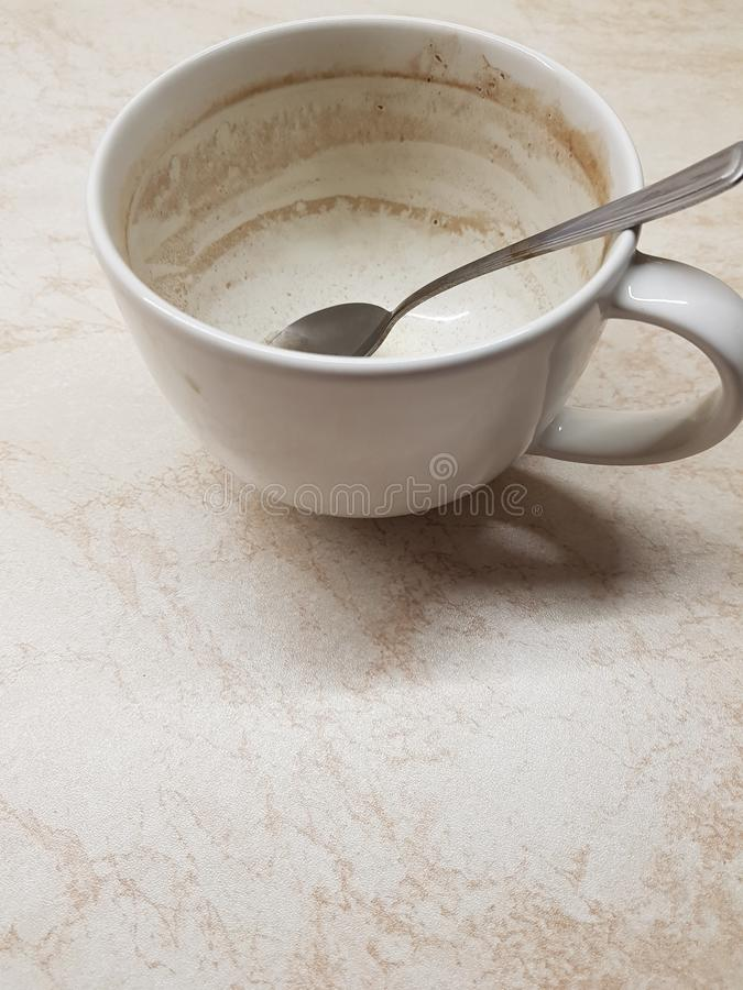 Dirty white mug. With a spoon, empty mug is in the kitchen, finished black tea royalty free stock image