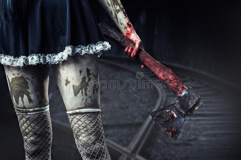 Dirty womans hand holding a bloody axe royalty free stock photography