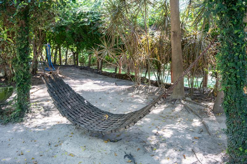 Dirty wood hammock made from black PU foam in backyard. With sand ground stock photography