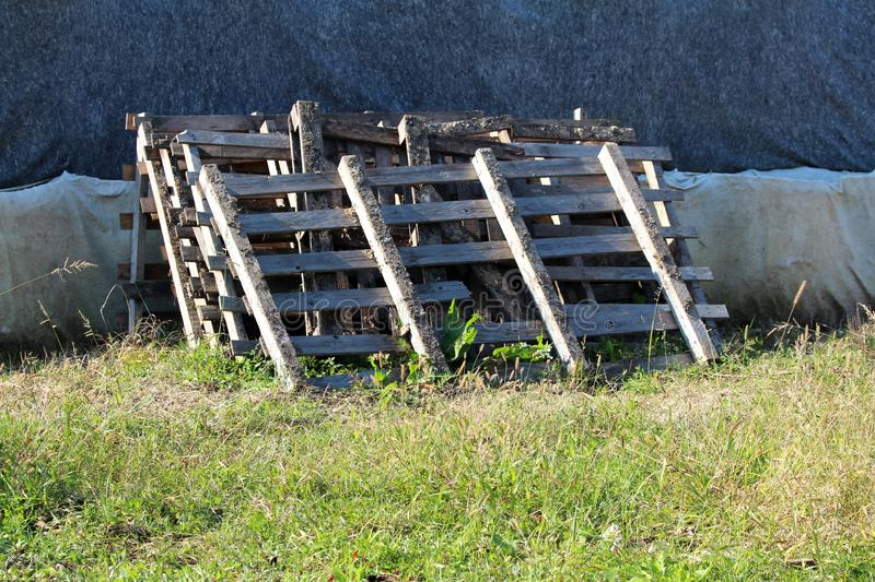 Dirty wooden pallets stacked together on single pile leaned on box barriers covered with geotextile fabric surrounded with high royalty free stock image