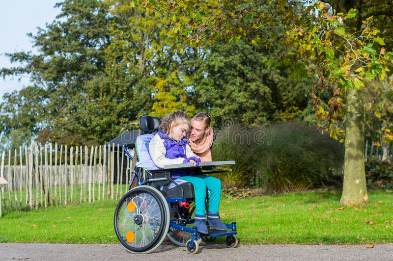 Disabled girl in a wheelchair relaxing outside royalty free stock photo