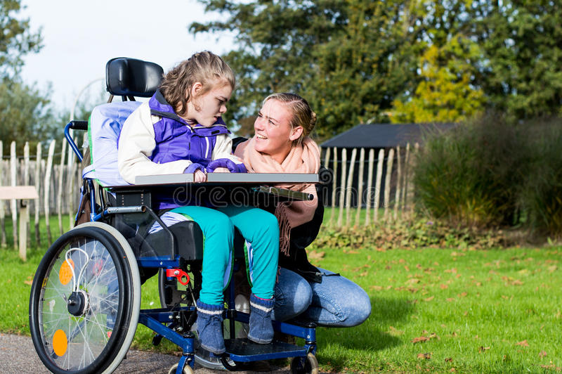 Disabled girl in a wheelchair relaxing outside stock photos