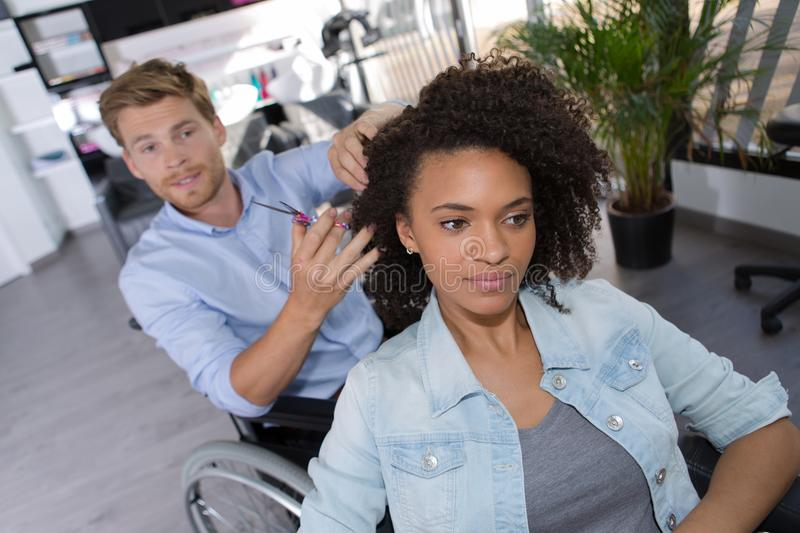 Disability man cutting customers hair stock photography