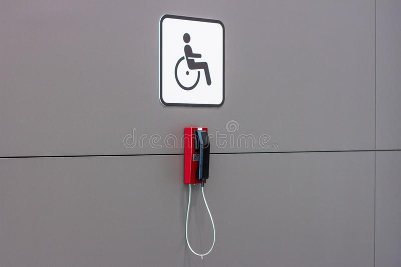 Disability sign with wheel chair and red emergency call phone on gray wall background. Accessibility handicap people equipment con stock images