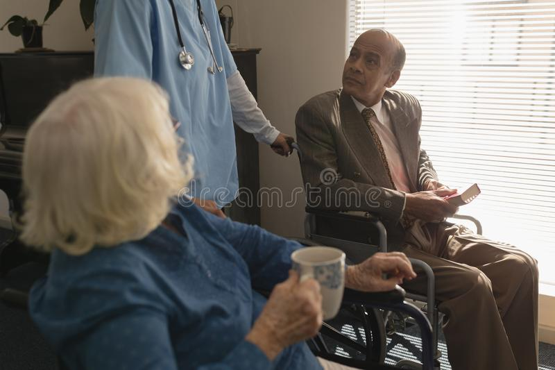 Disable senior couple talking with doctor at home royalty free stock image