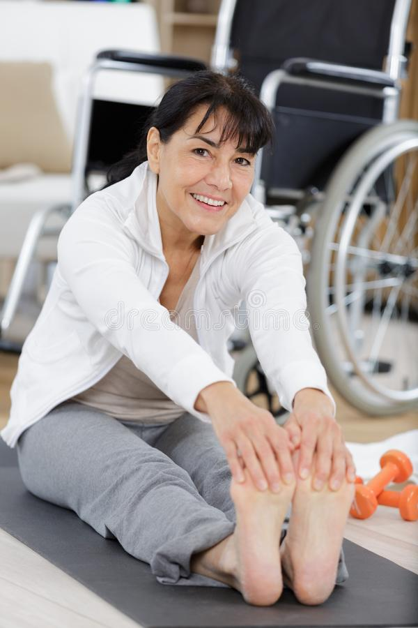 Disable woman stretching legs indoors stock images