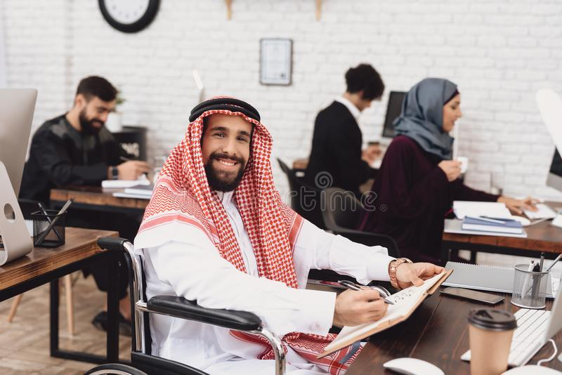 Disabled arab man in wheelchair working in office. Man is taking notes. stock photos