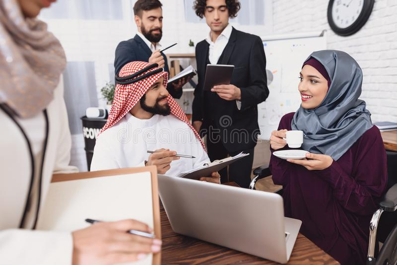 Disabled arab woman in wheelchair working in office. Woman is drinking coffe and talking to coworkers. royalty free stock photo