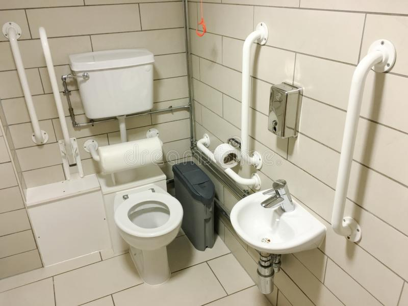Disabled assisted bathroom toilet neutral tiles and white grab rails. Uk royalty free stock photos