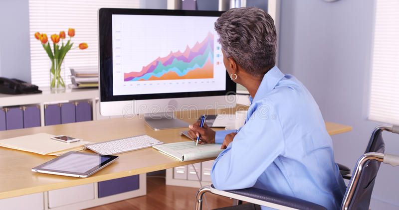 Disabled black businesswoman working at desk royalty free stock photo