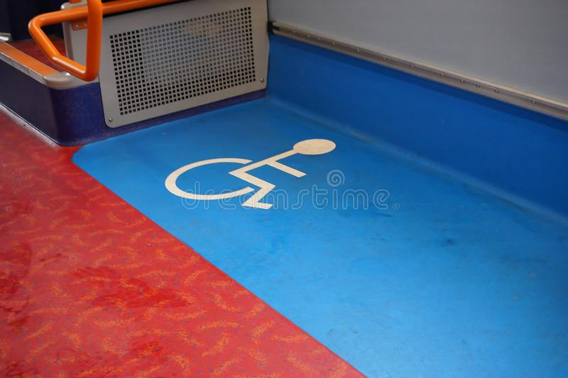Disabled blue and white sign on floor of a public transport bus royalty free stock photos
