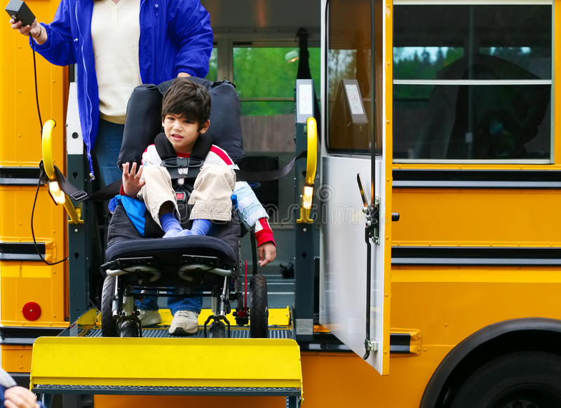Disabled boy on bus wheelchair lift royalty free stock photography